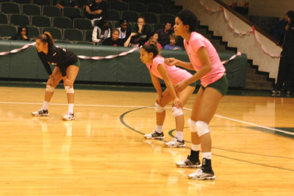 Crouching into position, Jazlyn Smith, Diamond Aguinaldo and Maritza Mesa are waiting for a serve to come their way. Mesa scored 13 kills on Barton over the course of four games.
