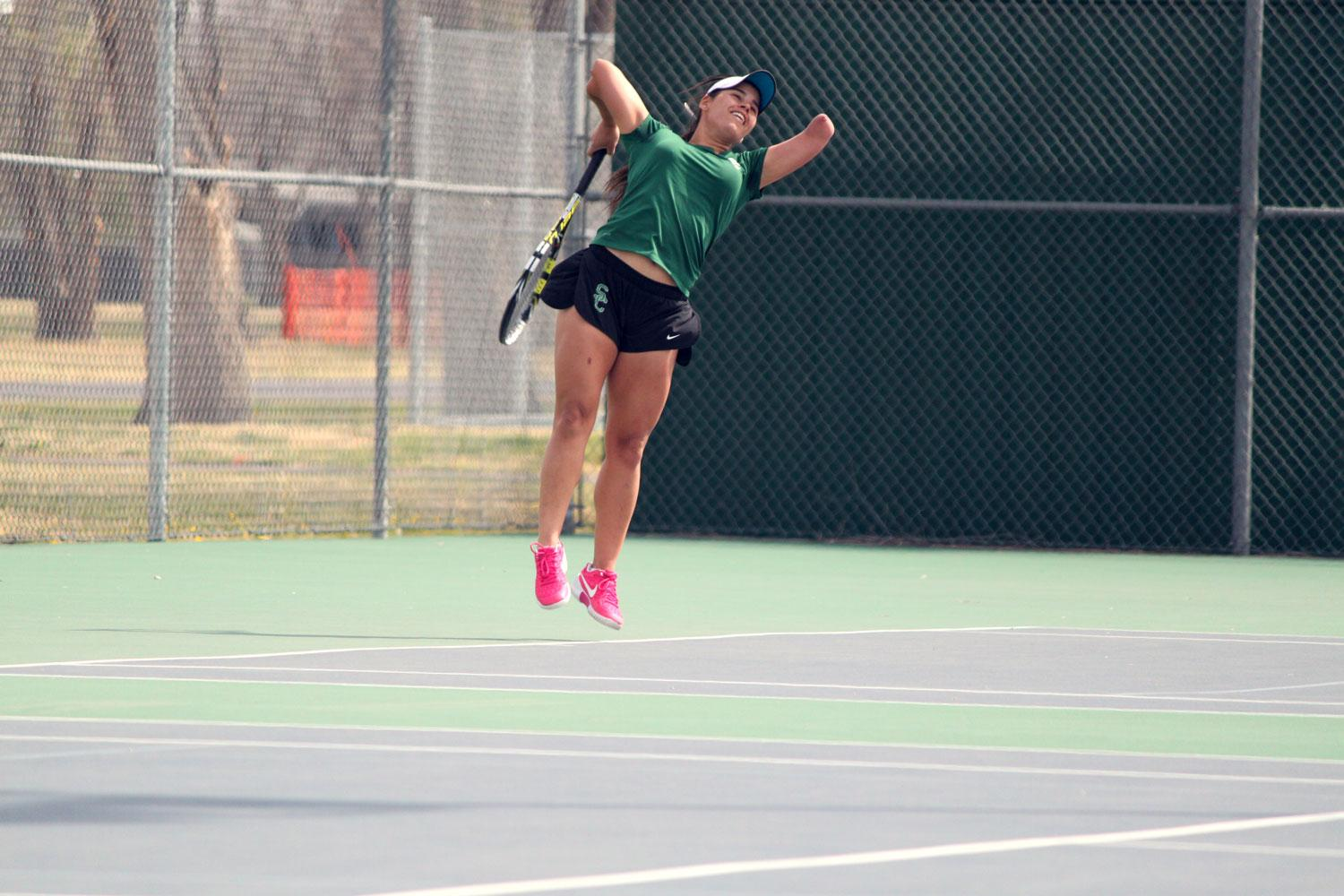 Sophomore Thalita Rodrigues powers up for a serve. Rodrigues had a great first season in Liberal for the Lady Saints winning Region VI Championships in both singles and doubles while placing in the top five at the NJCAA National Tournament in both as well.