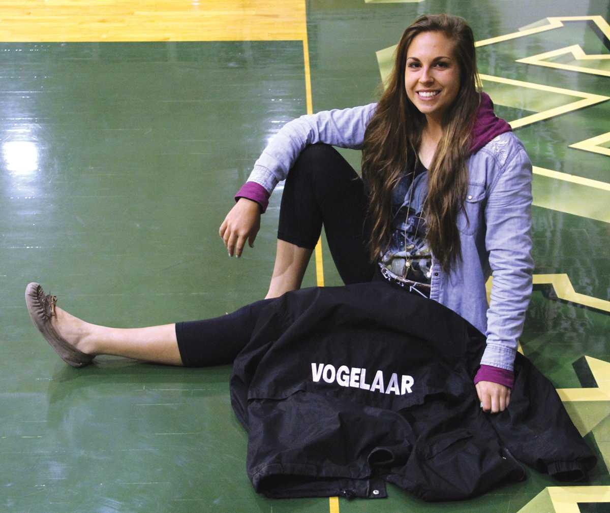 Crusader photo/ Maria Lara Freshman softball player Felisha Vogelaar shows her softball pride as she sits with her softball jacket before  an interview.