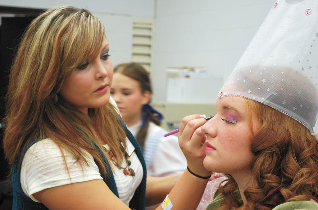 "Crusader photo/Alfredo  Anaya Jandi Riddle applies makeup to Heather Grant who portrayed Glinda in ""The  Wizard  of Oz."""