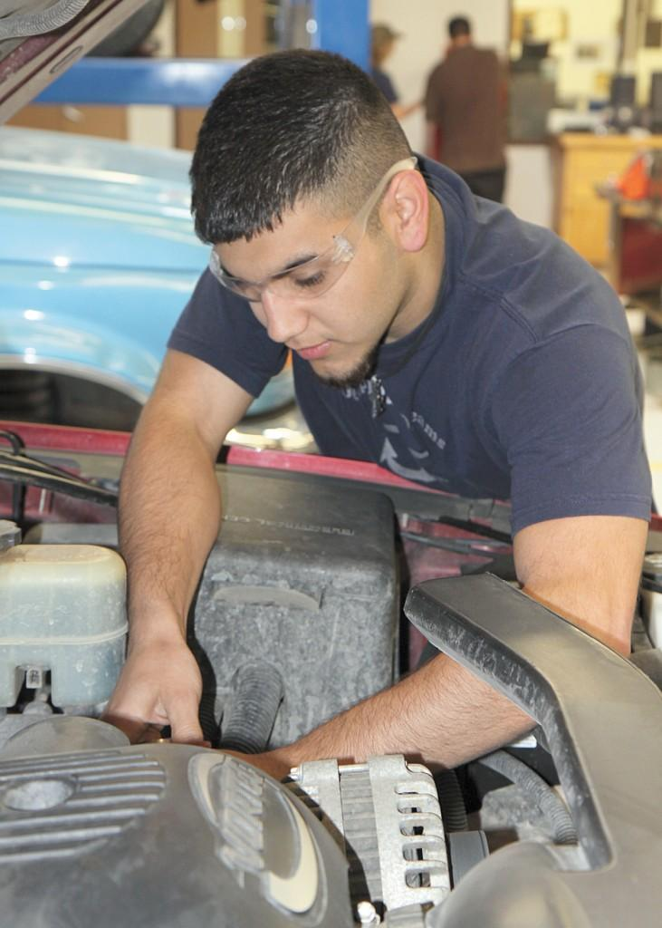 Crusader photo/ Landry Mastellar Acosta works under the hood of a car in the auto mechanics workshop at the Area Technical School. Acosta is an automotive mechanic technology major.