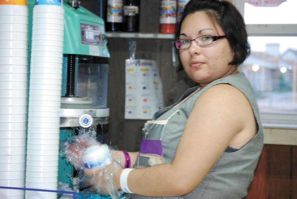 Heidy Molina makes a snow cone at the Sno Shack, a job she worked all summer.