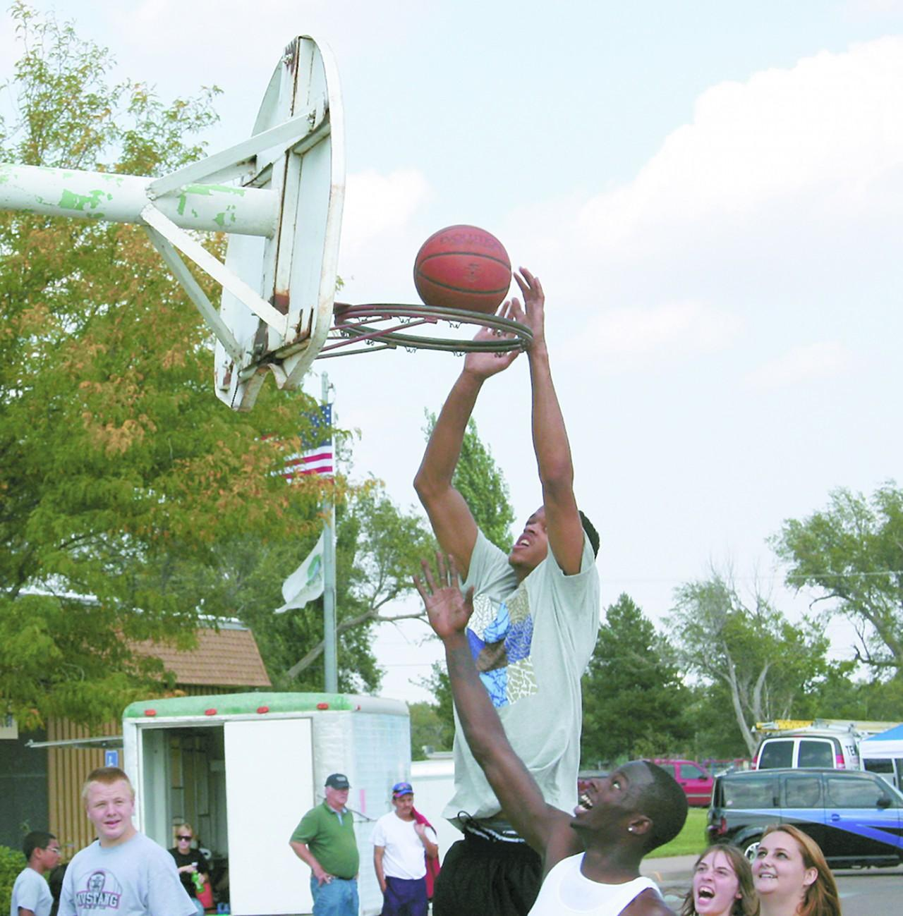 Crusader photo/ Will Rector Jon Tassin slam dunks a basketball during the Play a Saint event at the Chili Cookoff.