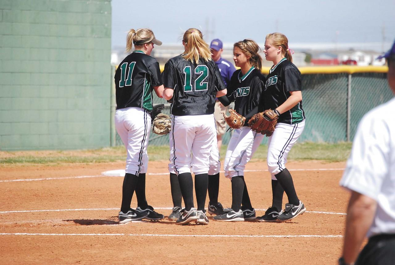 The infield huddles around pitcher Erin Roufosse after an out is recorded in the third inning Tuesday.