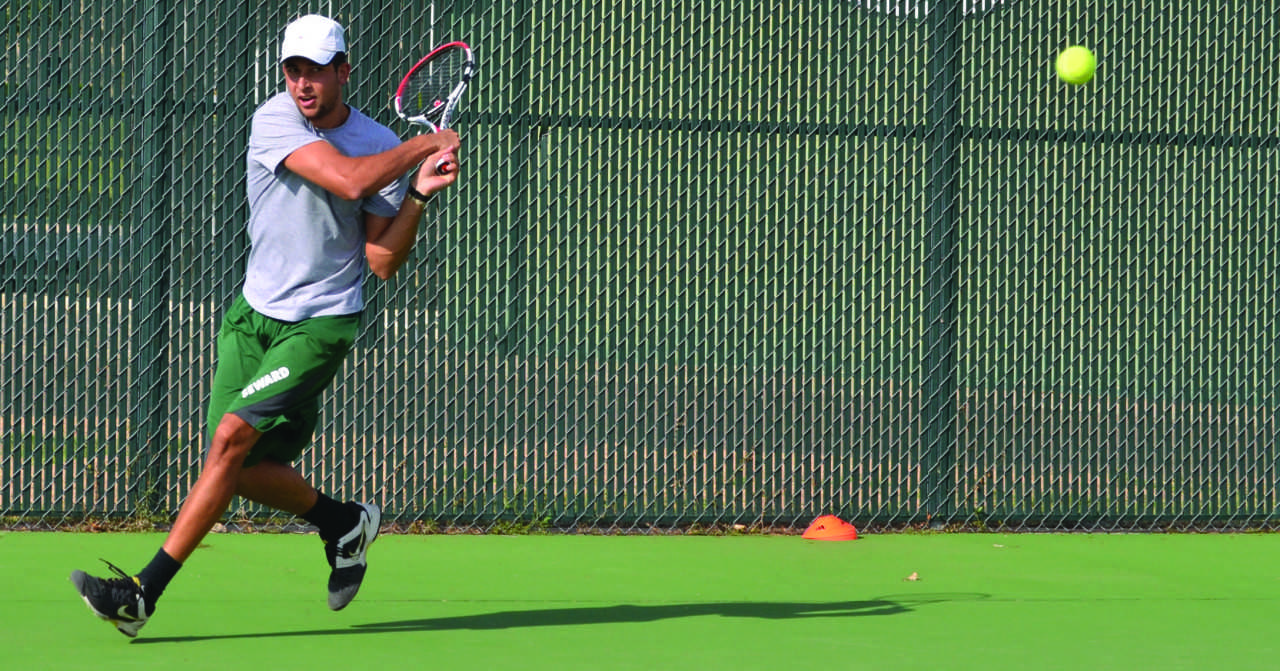 Sophomore Justin Pena returns a ball during the Saints Tennis practice.