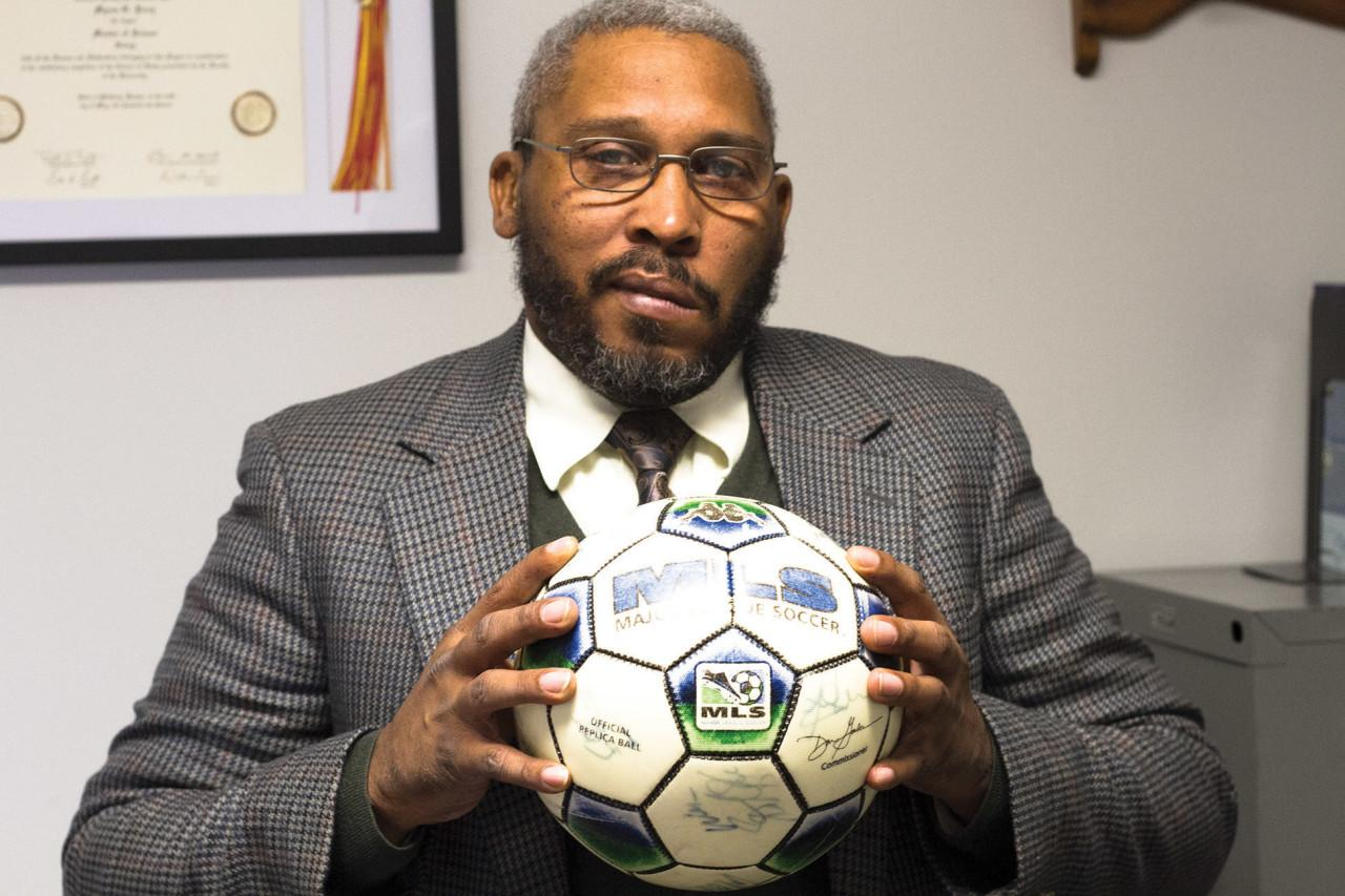 Myron Perry holds up a Major League Soccer ball. Perry played  professionally as a goalkeeper for two years before teaching at Seward.