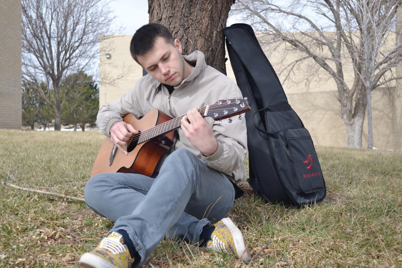 Nathaniel James Lee playing his guitar at SCCC campus.