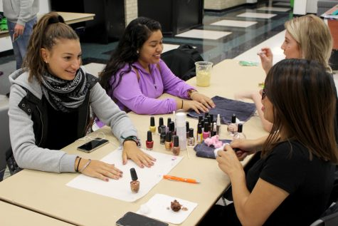 Tennis player Sarah Manseri is treating herself to a manicure provided by a Cosmetology student.