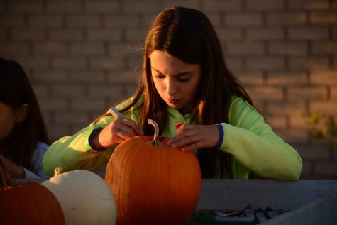 Ana Pepa carves a pumpkin to enter the pumpkin carving contest at the Pupmkin Olympics. Ana is only 11 years old and attended the Pumpkin Olympics with her parents.