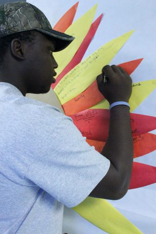 Kenny Holmes, HVAC student, writes what he is thankful for on the Admissions bulletin board.