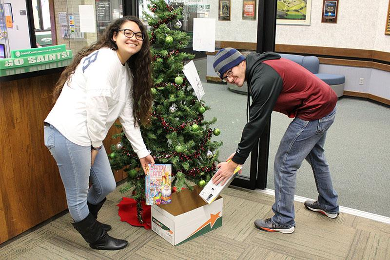 SCCC students Andrea Andrea Urbina and Myles Hall, donate gifts to give back to kids.