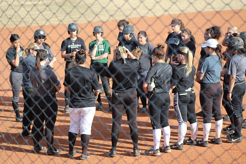 Lady saints softball team get a pep talk from their coach before starting practice.