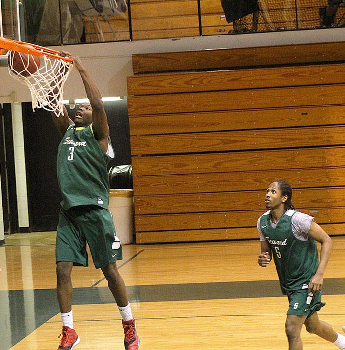 Sophomore Ernest Carter, finishes a play with a slam dunk from a assist from teammate Jeromie Simmons.