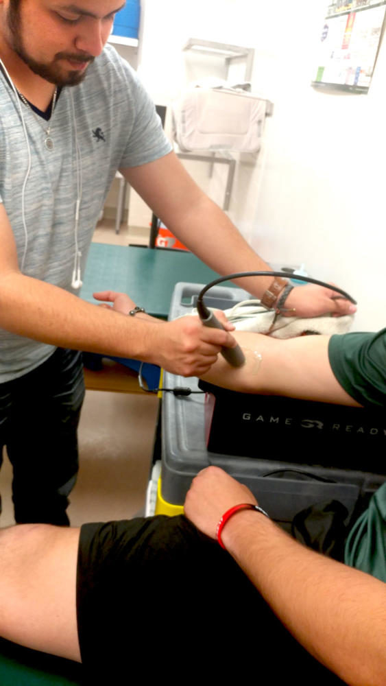 Sammir Martinez, student athletic trainer at SCCC, does an MRI on a baseball player's bicep and triceps.