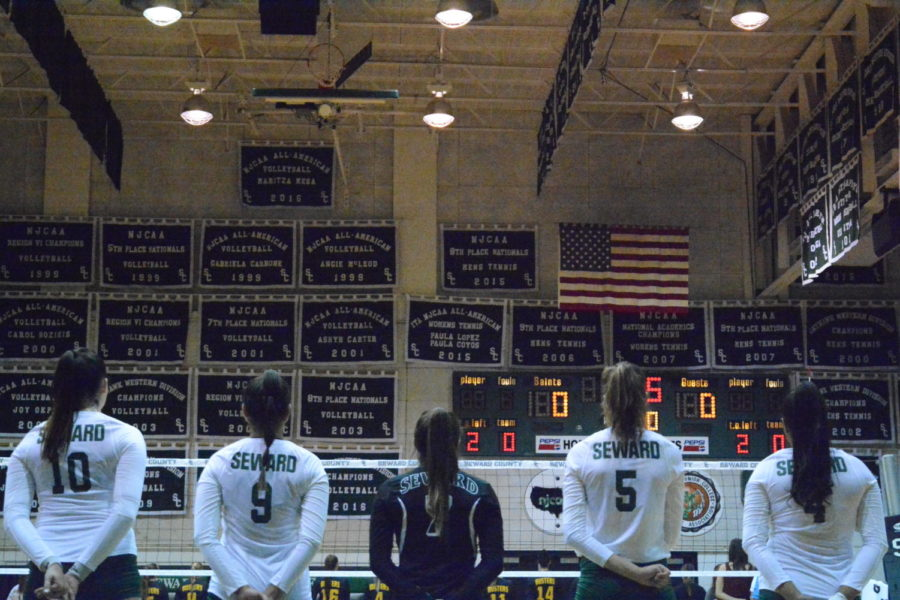 The Lady Saints line up for a pre-season game for the National Anthem. The banners in the Greenhouse are constant reminders of what's expected of their team — to win championships.