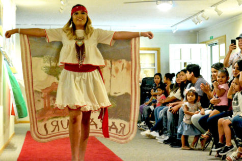 Sarahi Aguilera struts down the runway showing off her outfit. The Baker Arts Center put together a fashion show to highlight different cultures and styles in honor of Hispanic Heritage month that runs from Sept. 15- Oct. 15.
