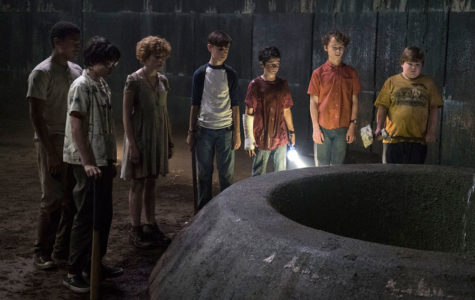 The seven children from the movie watch Pennywise descend down the tunnel.