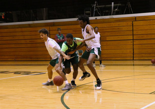 Freshman Jamel Horton attempts to dribble in between defenders Anthony Thomas and Isiah Small. The team was scrimmaging half-court and mainly focusing on attacking to the basket.
