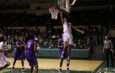 Freshman Mohamed Selmi soars in the air to lay it up in the basket.  (File photo)