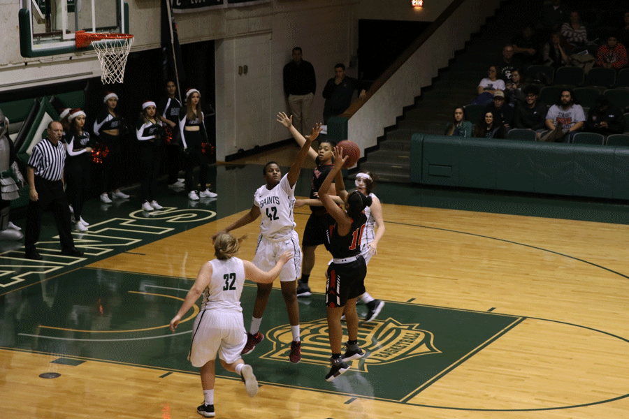 Freshman Carla Covane blocks a Red Devils shot during the first half. Carla Covane finished the game with 11 points, seven rebounds, two assists and steals.