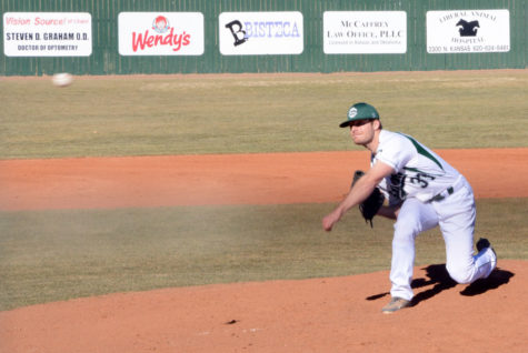 Ethan Earhart pitches a few practice throws before the game starts. Earhart pitched three of the nine innings.