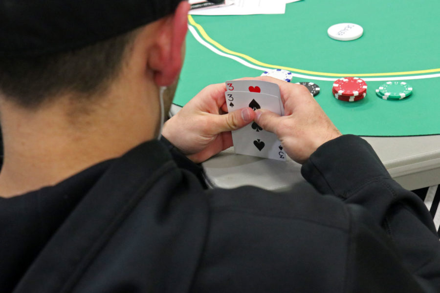 A student checks his cards. He doesn't have many chips left and has to be cautious or bluff. He ended up folding this hand.