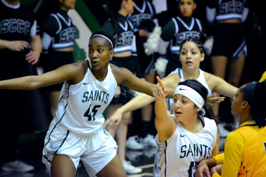 Twins, Vanessa and Valerie Caro, along with Vilma Covane, play defense against Garden City. Seward was on top during the game, with Garden City falling behind.