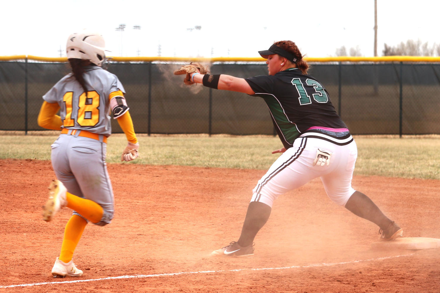 Freshman first baseman, Madeline Owen, prepares to catch a ball and get a Broncbuster opponent out on first.