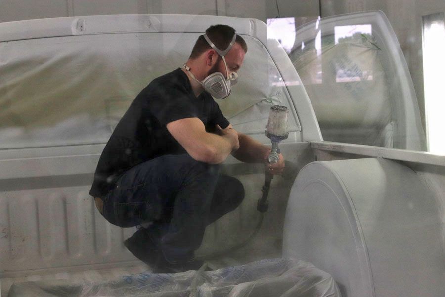 Damian Romero paints the sides of the bed and coats them with an even layer of paint. Students in the autobody class are expected to wear respirator masks when priming and painting and safety glasses when in the shop. A plexiglass wall keeps paint from getting on other items in the shop and allows for others to watch.