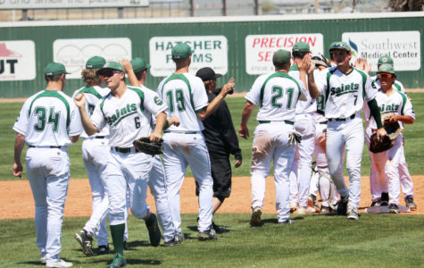 The Saints baseball team comes together and congratulates one another after their 8-2 win over the Blue Dragons.