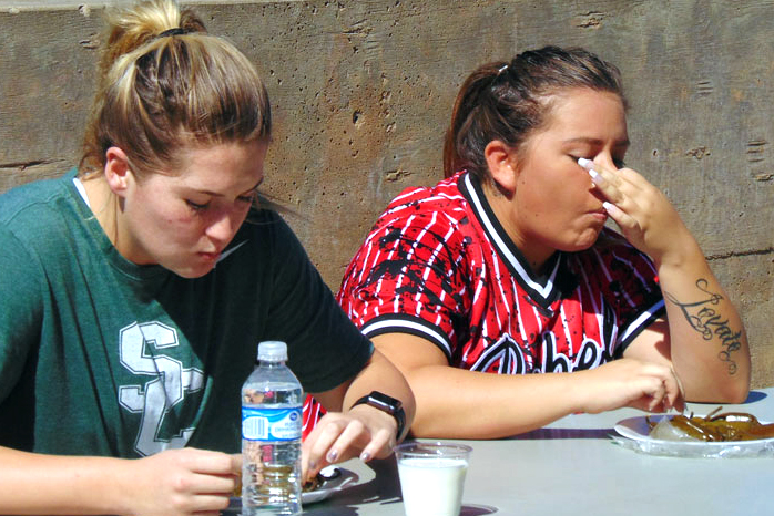 Taylor Parker, Accounting major from Hooker Oklahoma, and Abby Lovato, Liberal education major, stuff Jalapeños as fast as they can into their mouths at the annual contest on Oct 5. Hooker won first place.