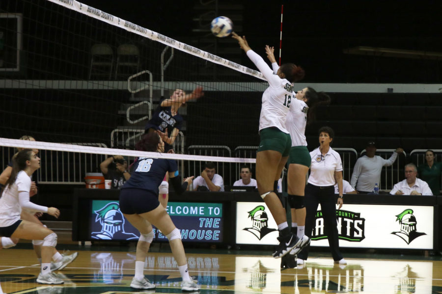 Sophomore middle, Luz Sierra and freshman setter, Laura De Pra block a hit against Colby. (File Photo)
