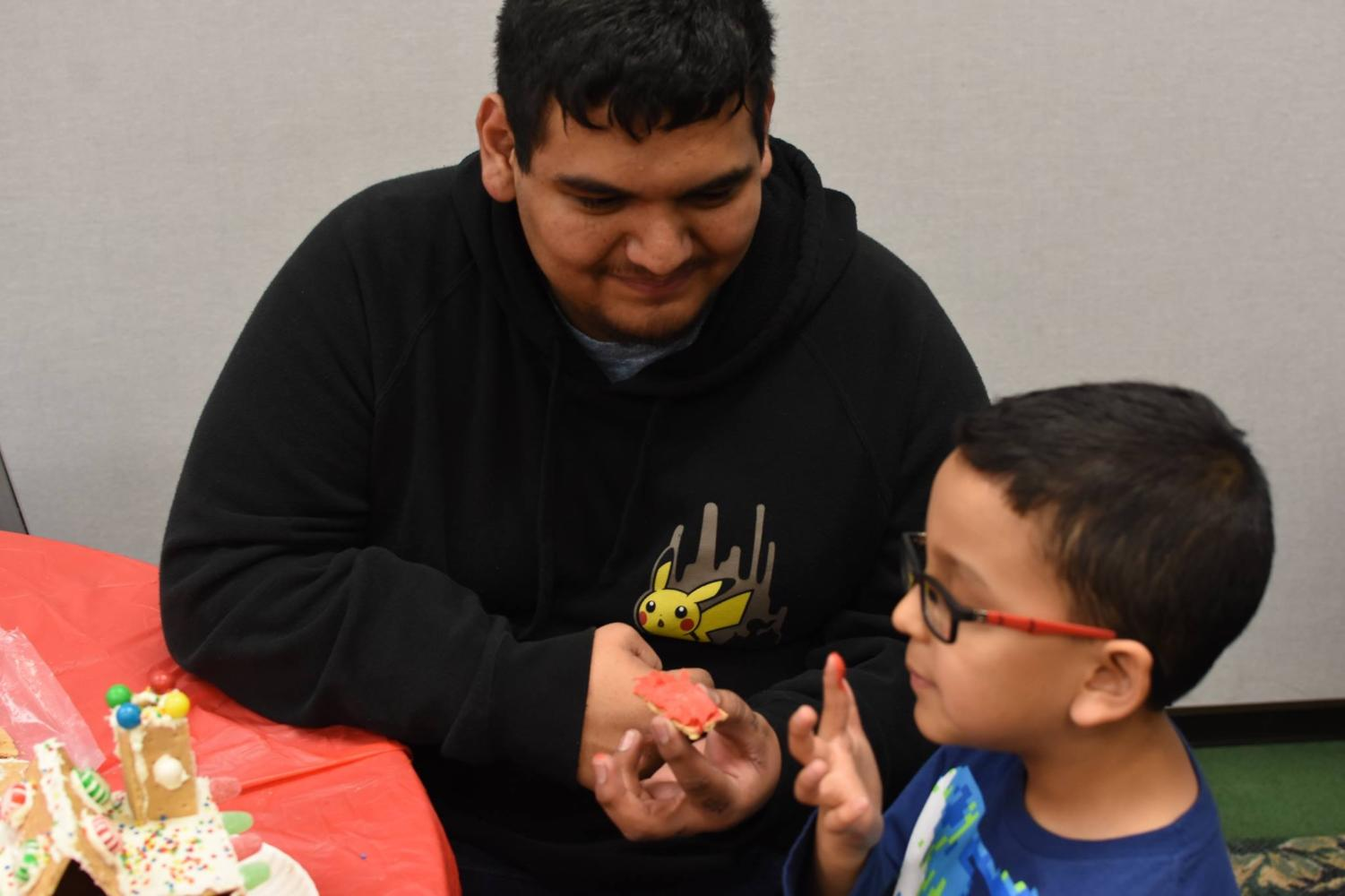 Danny Vasquez, Liberal drafting major, helps a grade schooler build a gingerbread house. Vasquez is part of the new club, Circle K International. The club is dedicated to community service and helping others.