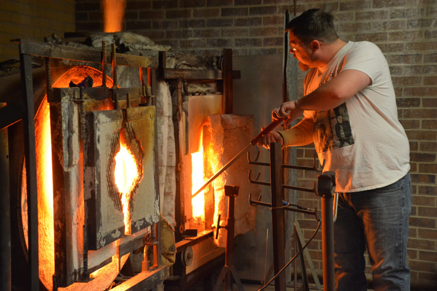 Matthew Williams demonstrates how to gather glass to the end of the blow pipe. He does this inside the furnace. He twirls the blowpipe in his hands at a medium pace.