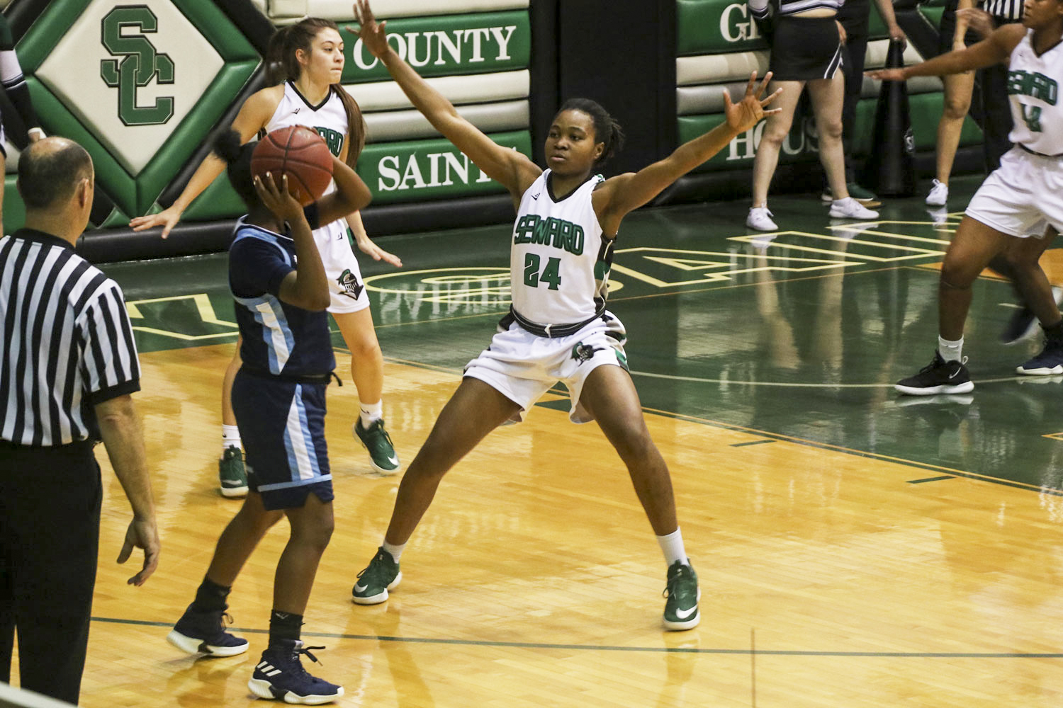 Vonda Cuamba plays good defense to help the Lady Saints defeat the Lady Trojans, 65-60. The win extended their win streak to 19 in a row.