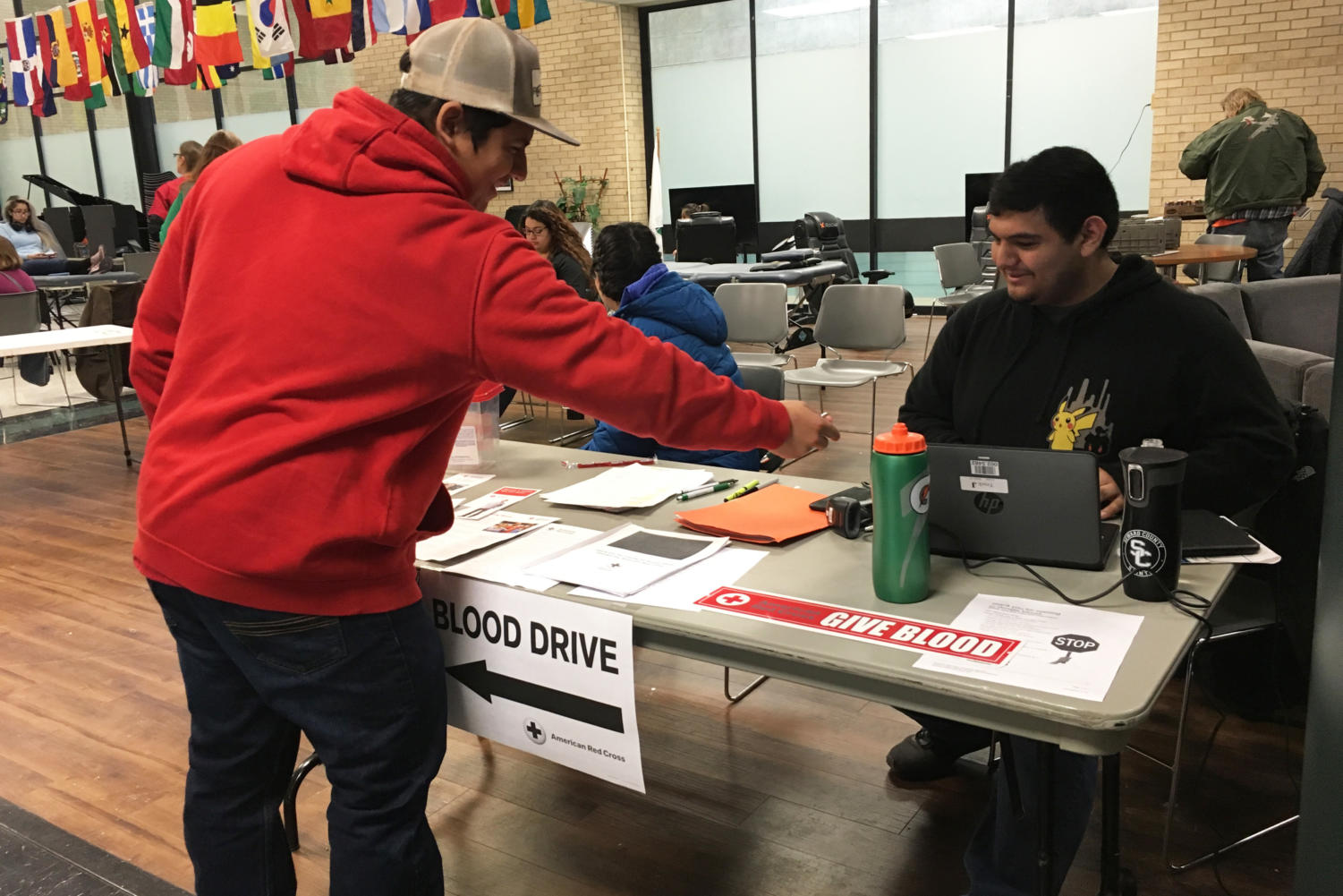 Adan Gonzalez is working as a volunteer at the blood drive. Jonathan Ibarra  is signing in to donate blood and save lives.