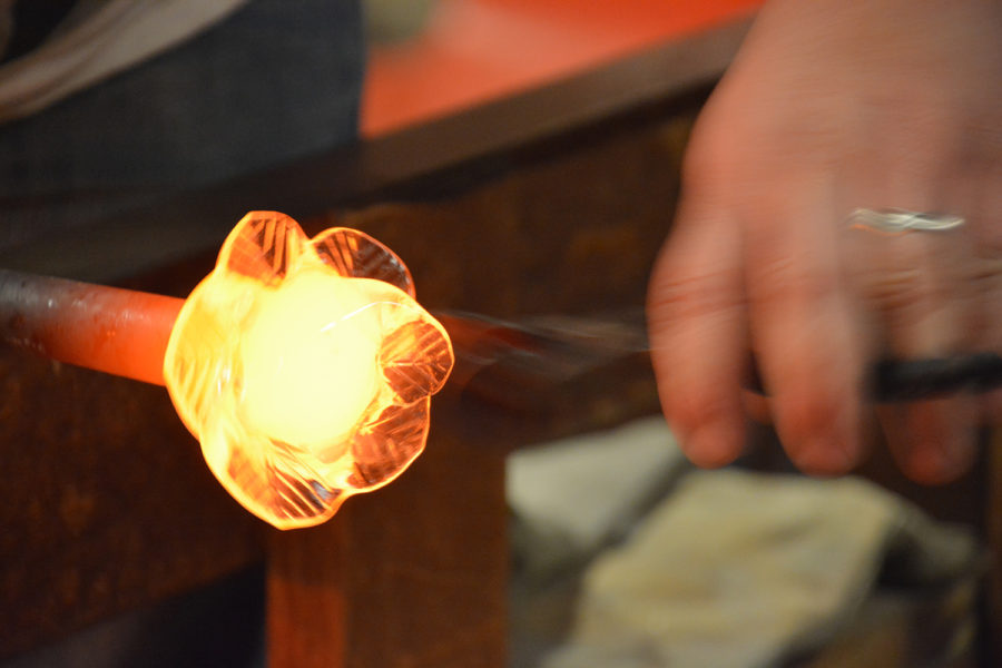 Matthew Williams finishes the rose by creating the petals of the rose with a tool called a leaf masher. He works fast because of the need to keep the glass hot.