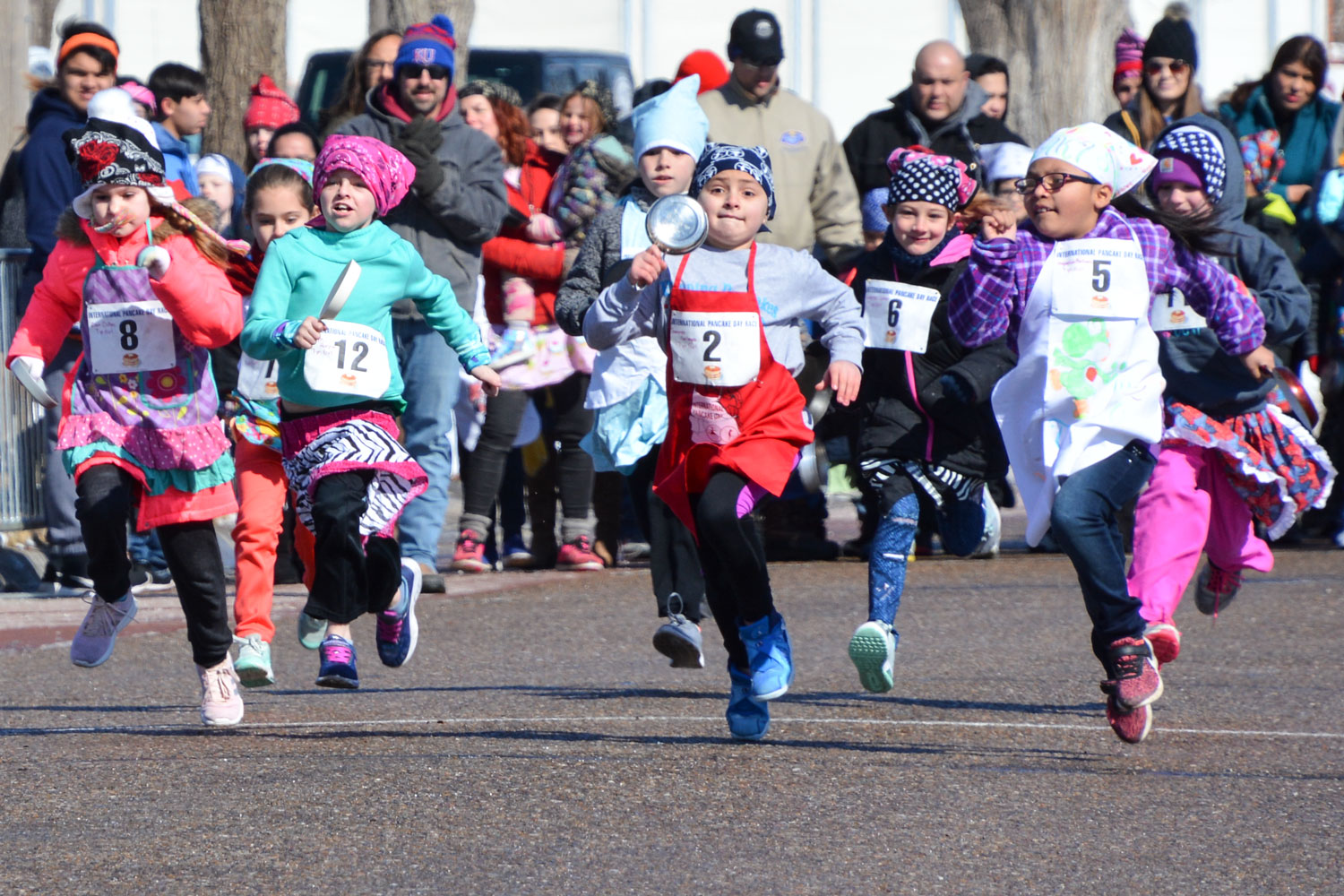 The+kids+race+to+the+finish+line+wearing+aprons+and+carrying+a+frying+pan.+These+pre-races+are+a+tradition+at+Pancake+Day.+Children+and+even+men+race+before+the+main+event+-+the+Last+Chance+Race.+All+of+the+racers+wear+aprons%2C+headscarves+and+run+with+frying+pans+and+a+pancake.