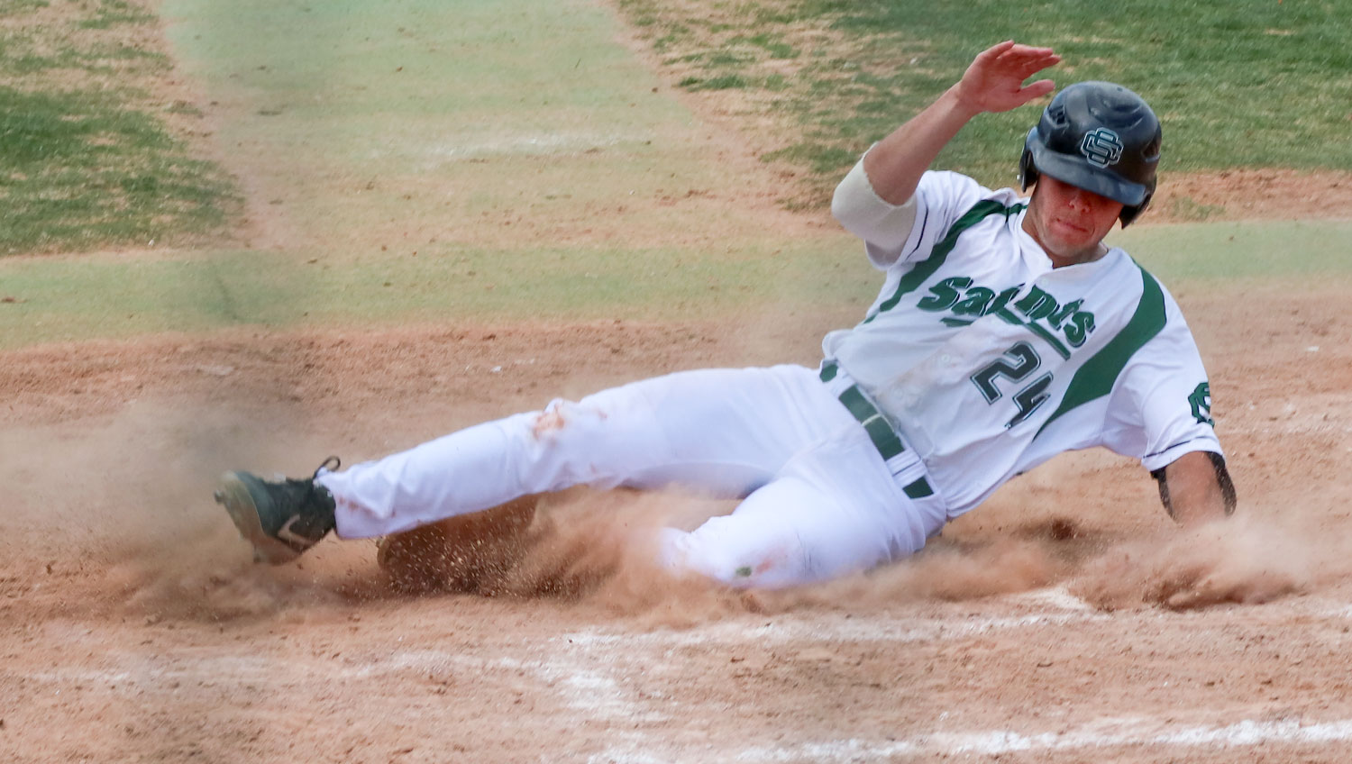 Sliding+across+home+plate%2C+Benny+Ayala+scores+a+run+for+the+Saints+midway+through+the+nine+inning+game.+%0A