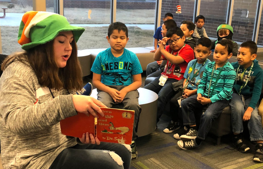 Cheyenne Miller, reporter, reads to a group of first graders as part of Dr. Seuss Week. Crusader staff woke up early to spend time before classes with the elementary students.