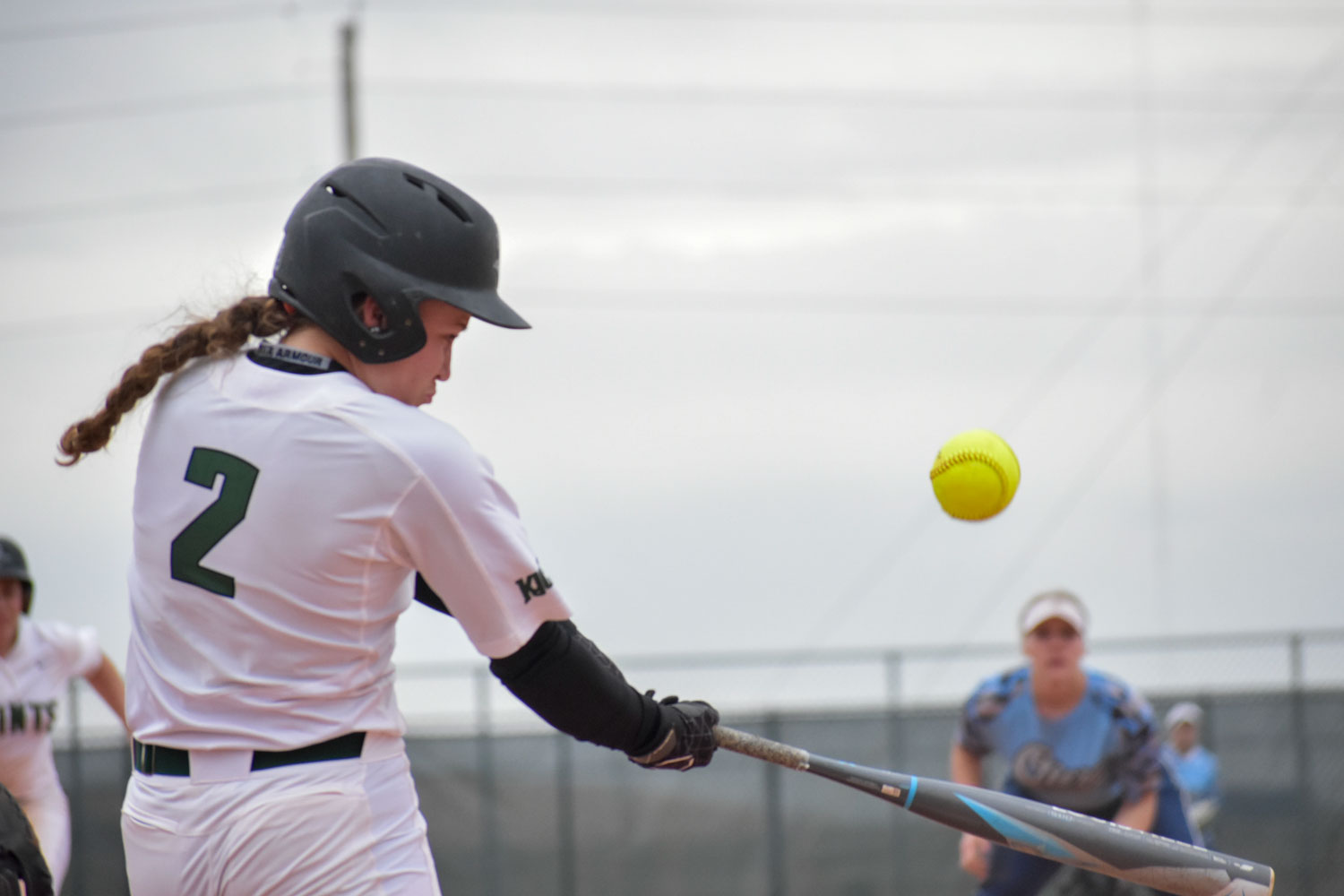 Jaci Oakley, freshman infielder, pops a shallow fly ball between third and left field for her first hit of the game April 3, against Otero Junior College. The Lady Saints split the doubleheader losing the first game, 3-7, but won the second, 10-5.