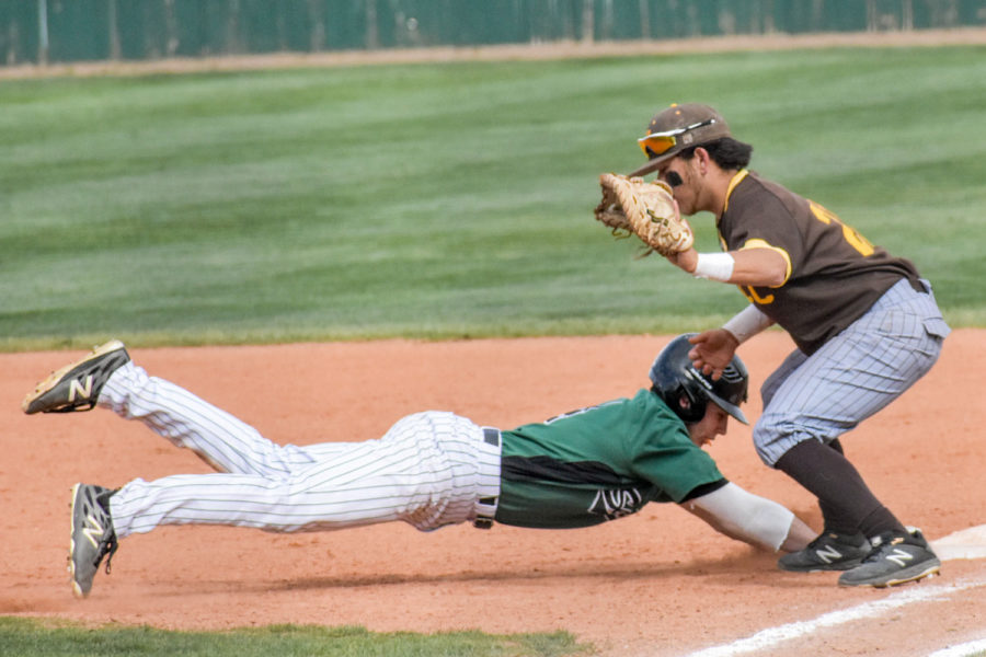 Zane Alexander, Del City, Oklahoma freshman, dives bad to first base. The outfielder is known for his speed and large leads off the bag, driving opposing pitchers crazy. Alexander added two hits towards the end of the game ensuring that Seward takes a doubleheader win.