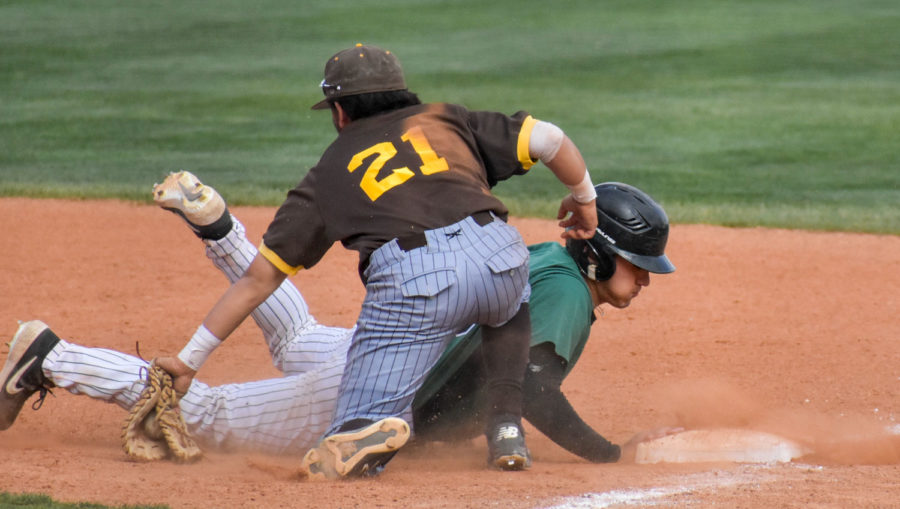 Zane Alexander dives back to the bag from a long lead off. He touched the base just seconds before the Garden City Community College first baseman tagged him. Alexander drove the opposing pitcher crazy on the base path.