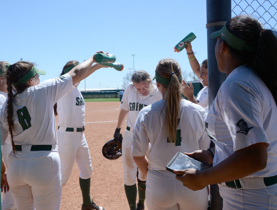 Jaci Oakley is greeted by teammates with a dousing of water after hitting a homerun against Northwest Technical College.