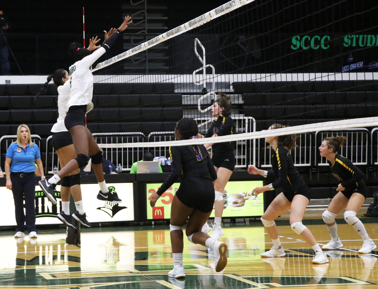 Two Lady Saints gnail a block against the Lady Conqs in Wednesday's game. Seward won in convincing fashion, 3-0.