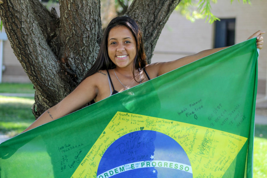 Freshman biology major, Victoria Martins, proudly holds up the flag of her home country, Brazil, as she poses for a picture. Signatures from her friends in America and her hometown, Sete Lagoas, Brazil, paint the flag. When asked for a picture, Martins stated that she was not going to dress nice everyday so anytime would be good. Martins shared some of her culture and also recalled some American culture she found strange.