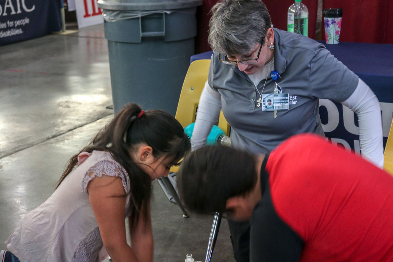 Elizabeth Irby, CPR/First Aid teacher of SWMC, has a couple of kids race each other doing CPR at the Community Health Fair.