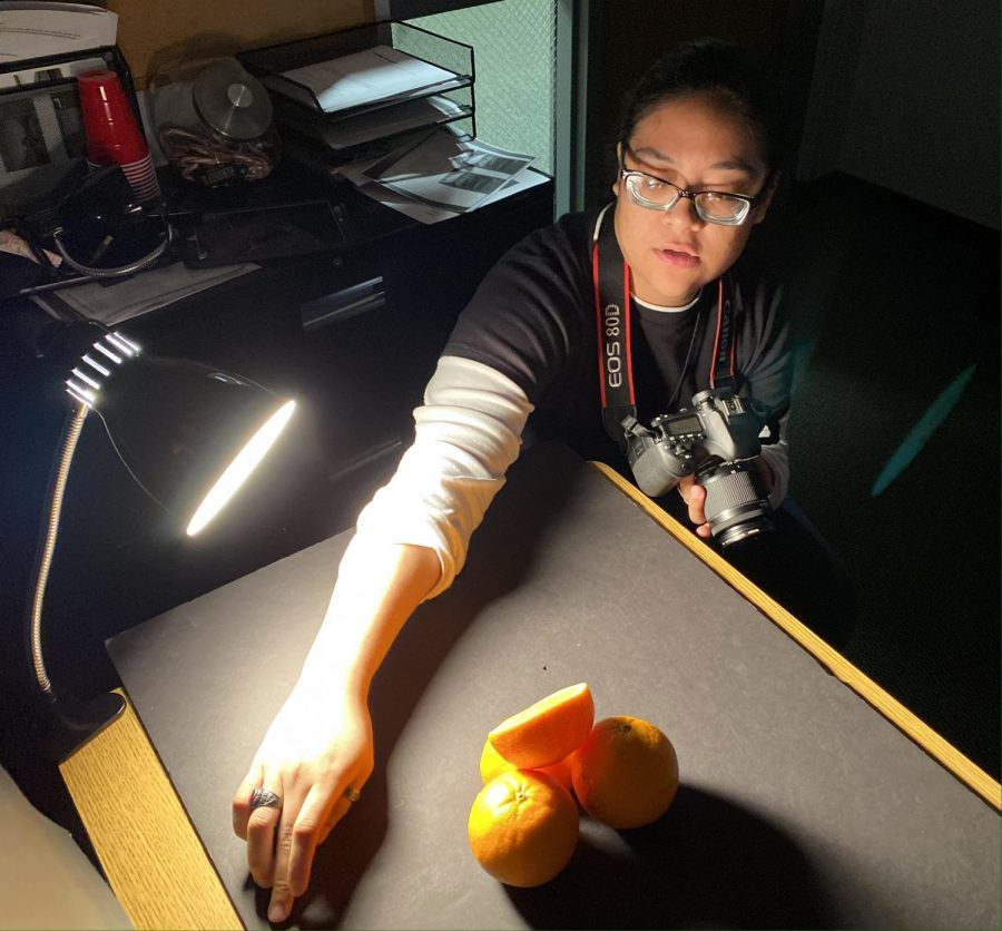 Maggie Ibarra, sophomore psychology major, adjust the light setup for a feature photo. The Garden City native has learned photography skills this spring semester.