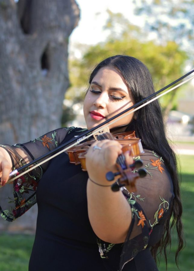 Dulce Perez plays her violin. The freshman music major shares an essay about her first love and trying to fit in at a new school.