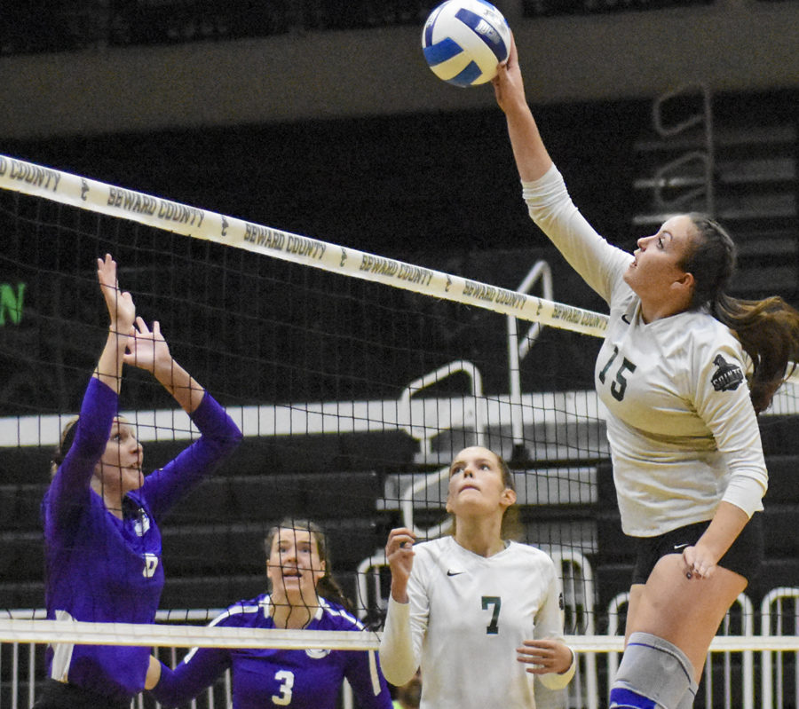 Thais Vieira, 15, gets the jump on blockers from Butler Community College. The sophomore from Brazil finessed the ball past the defenders for a score. The shot was set up by the Lady Saints sophomore setter Laura De Pra.